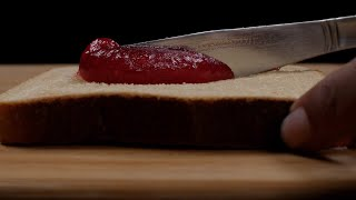 Low angle shot of a girl spreading jam over the top of a brown bread