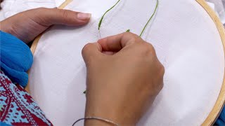 An Indian women / female doing embroidery with green thread
