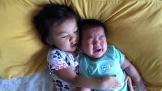 Big sister comforting crying baby brother