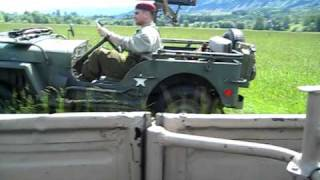 jeep and kubelwagen crossing field. former WWII enemys play together.