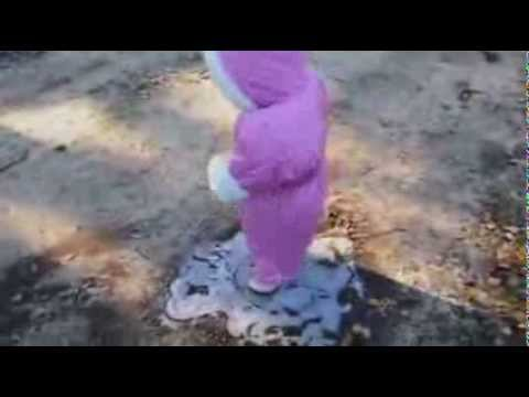Little girl in pink snow suit experiences ice for first time