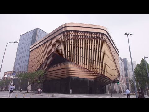 Бронзовая вуаль: в Шанхае фасад культурного центра украсили движущимися трубами
