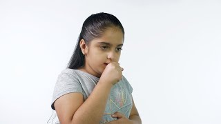 Little Indian girl is coughing against the white background - health care concept