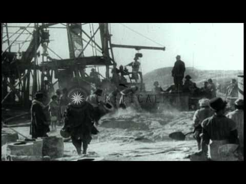 British geologist George B. Reynolds and workers drilling for oil and striking oi...HD Stock Footage