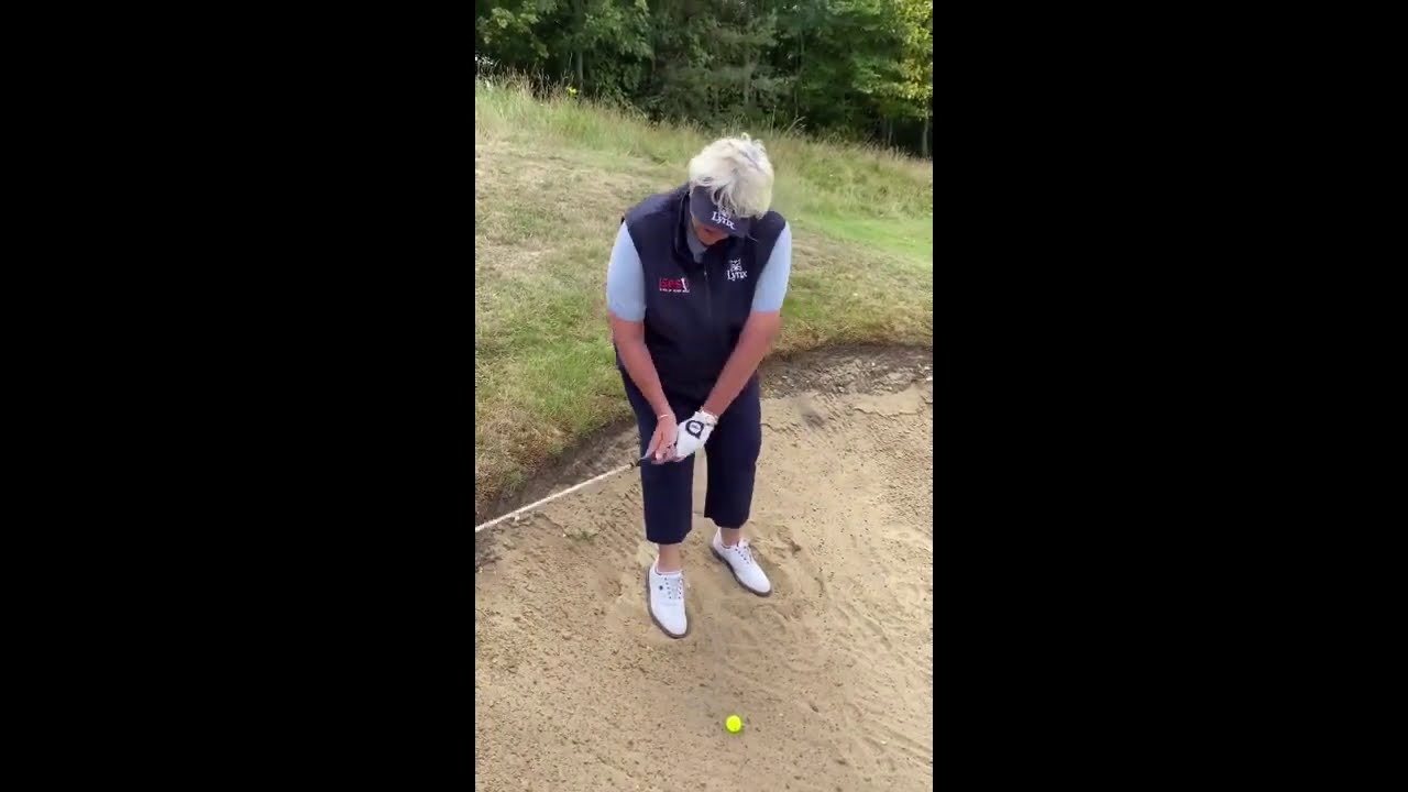 Downhill lie in a bunker with Dame Davies