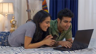 Cute Indian couple having fun together while using a laptop in bed - lifestyle couples
