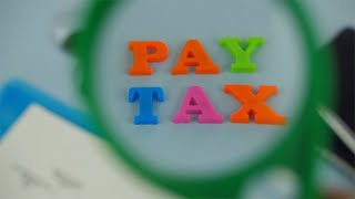 "Closeup shot of woman hands with a magnifying glass over the words ""pay tax"""