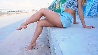 Pretty barefoot girl shows her feet and soles on the beach