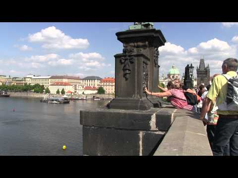 Rubbing dog and dame plaques on Charles Bridge, Prague