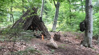Bushcraft deep in the forest:Tarp tent set up for the rain over the fire,Cooking roasted steaks etc.
