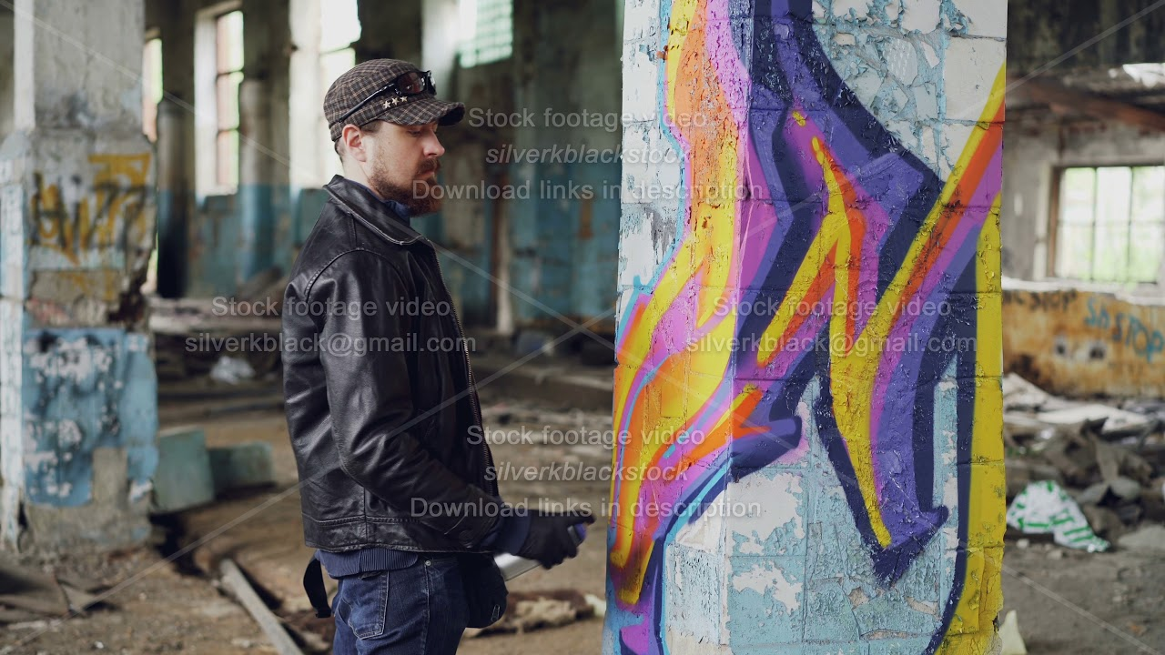 Professional graffiti painter is creating abstract image on large pillar inside abandoned building