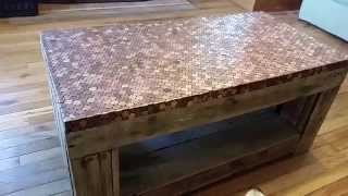 A Look At A Pallet Table Coated In Pennies
