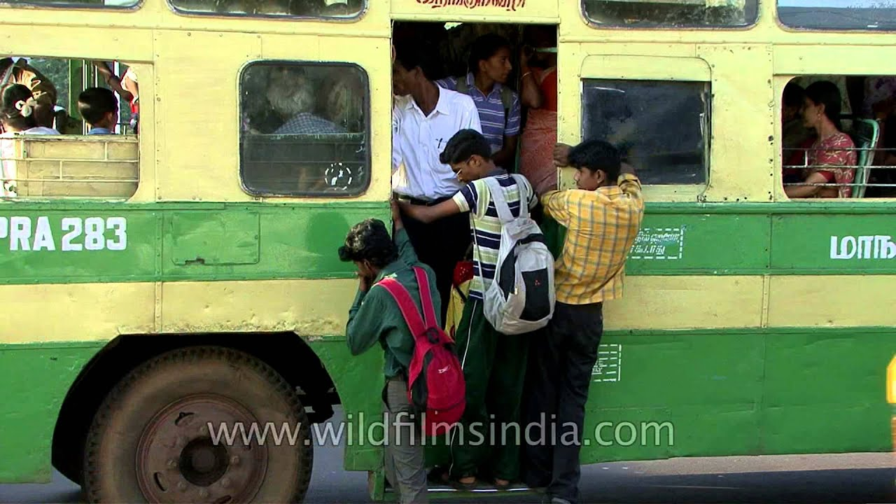 Traffic at Ripon building with Chennai bus travellers hanging out of old bus