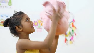 A cheerful little Indian girl playing with a plush teddy - closeup kids room. Childhood concept