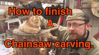 Finishing a chainsaw carving with power tools .