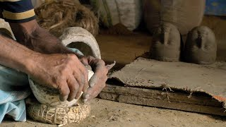 Pan shot of a man creating the face of the Durga idol with clay