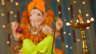 Low angle shot of Lord Ganesha idol on Ganesh Chaturthi - Indian Festival. Burning incense stick and lamp