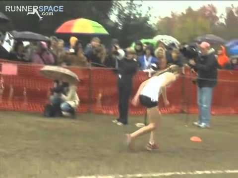 Runner crawls across finish line after collapsing.