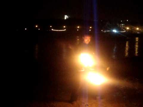 G spins fire poi on the Thames beach May 2011