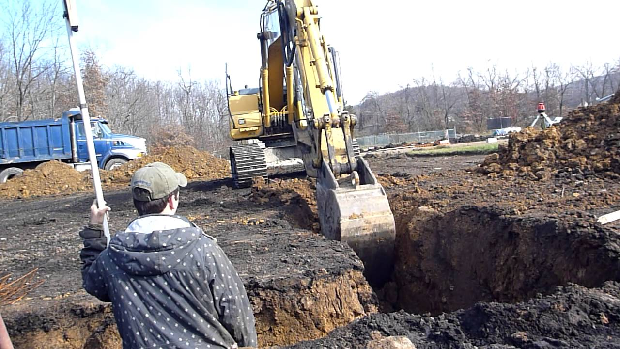 Komatsu excavator digging footers youtube for Digging foundation for house