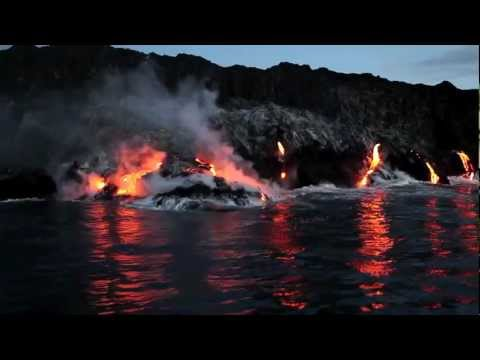 Lava pouring off cliffs into the sea in Hawaii Volcanoes National Park