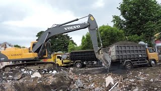 Excavator Volvo EC210B Pushing Overloaded Stuck Dump Trucks