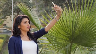 A girl standing in a park and taking selfie on her mobile phone