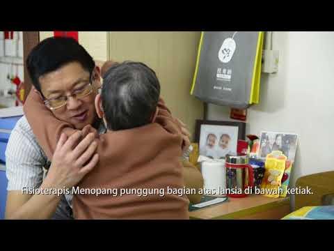 2 orang membantu lansia untuk pindah dari tempat tidur ke kursi oleh dua orang