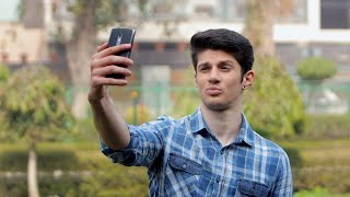 Mid shot of a handsome boy pouting and taking selfie photo using his phone outside in a park