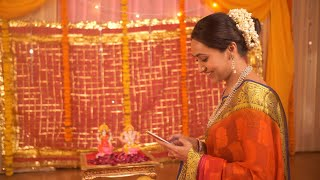 Attractive Indian woman texting using a smartphone before pooja begins at home - Festive Background