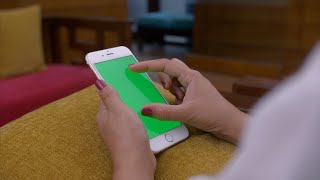 Woman scrolling the mobile phone screen with green screen
