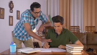Young Indian son discussing syllabus with father while studying at home - Parenting