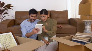 Young Indian couple sitting on floor - Exploring tab in midst of house shifting