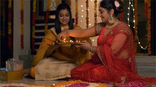Diwali festival decoration - Happy mother and daughter decorating rangoli with diyas