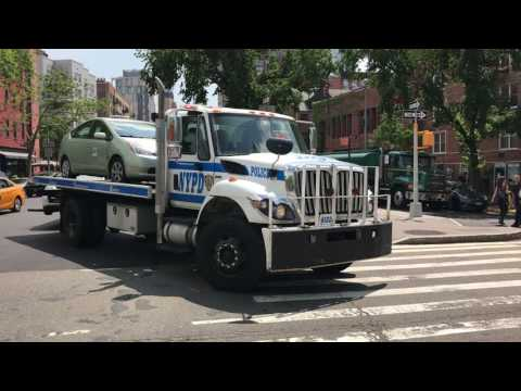 RARE CATCH OF A NYPD FLATBED TRUCK TOWING 2 DOT VEHICLES ON 6TH AVENUE IN SOHO, MANHATTAN, NEW YORK.