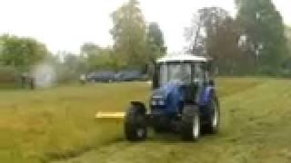 Ciągnik rolniczy FARMTRAC z kosiarką podczas pracy