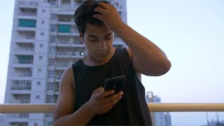Indian man / boy using his mobile phone in his room balcony
