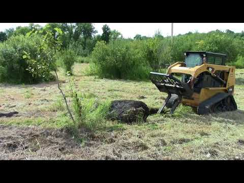 Caterpillar 247b 3 pulling large rocks out of field.