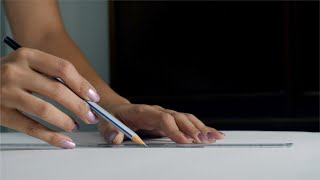 An engineering design student / girl drawing a straight line with ruler and pencil on a white sheet