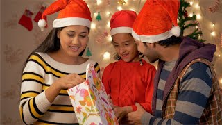 Happy Indian family opening the Christmas gift at home