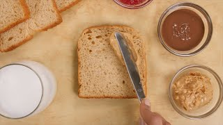 A girl spreading peanut butter on a slice of brown bread for a vegetable sandwich