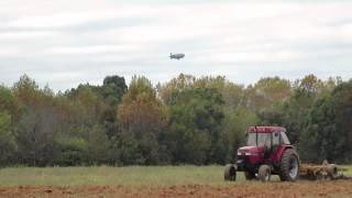 goodyear blimp flying over while case ih 5140 is pulling amco f17 disc