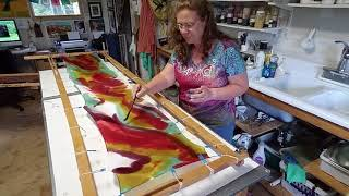 Hand painting a silk scarf.