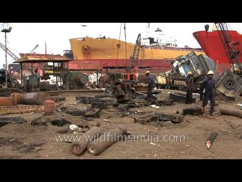 Labourers lift heavy metal structures on crane at a ship breaking yard in Alang