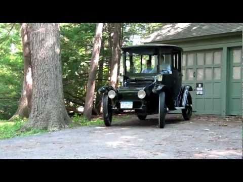 1914 Detroit Electric car drives silently away from its garage