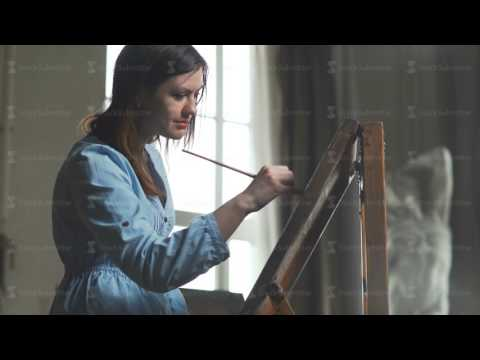 Professional artist working in brightly studio painting with brush
