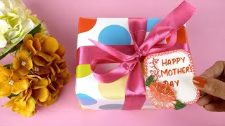 Hands of an Indian woman placing a 'Happy Mother's Day' tag on a colorful gift box