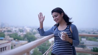Shot of an Indian girl smiling and waving at a friend from her house balcony