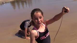 Young girl shows how to catch a beach worm for fishing bait