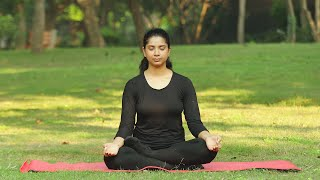 A young girl practicing kapalbhati (pranayama) yoga asana in a park